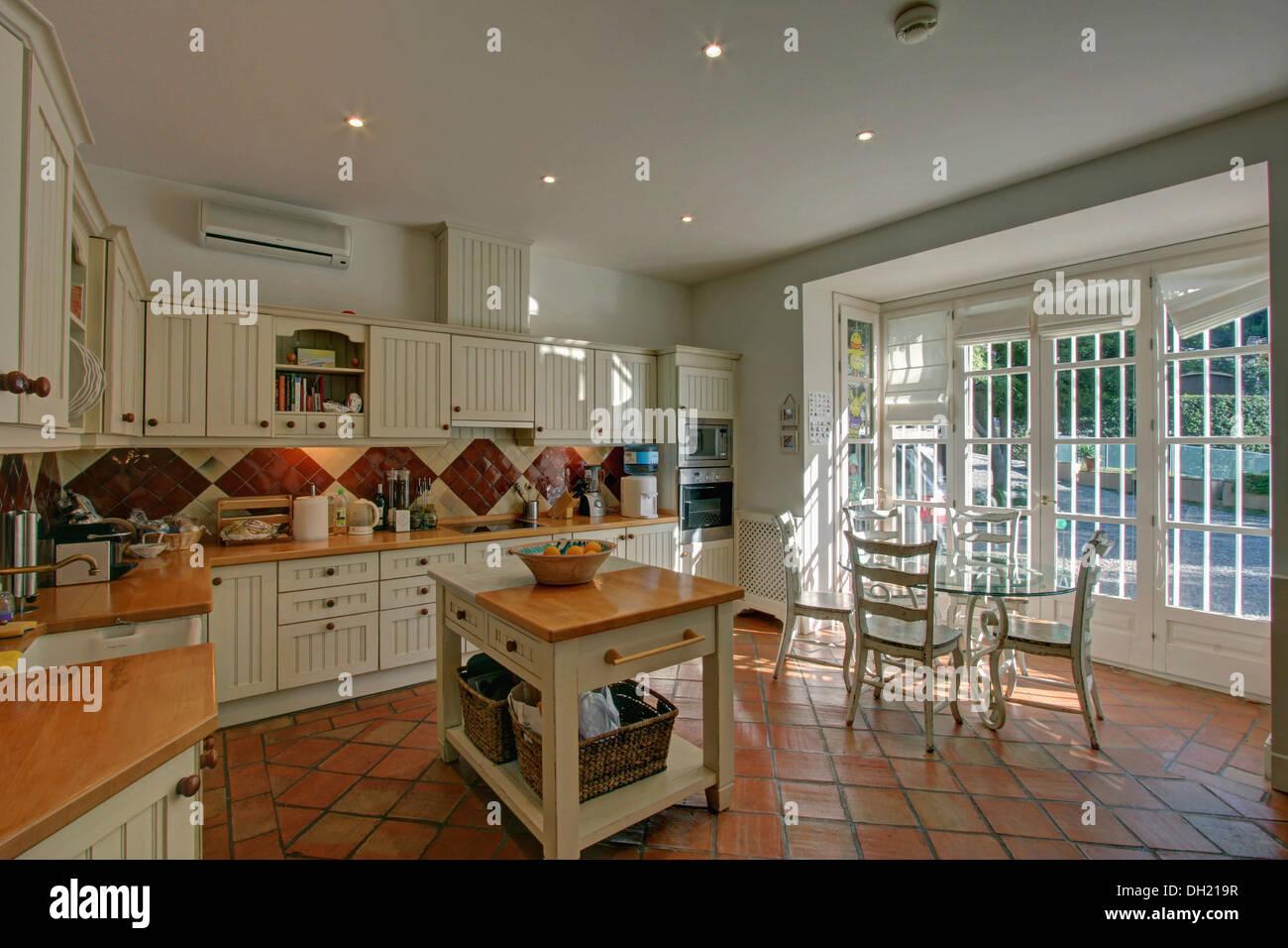 Metzgerei Block Im Landhausstil Spanische Küche Mit Terrakotta Geflieste  Boden Und Glas Esstisch Mit Weißen Stühlen