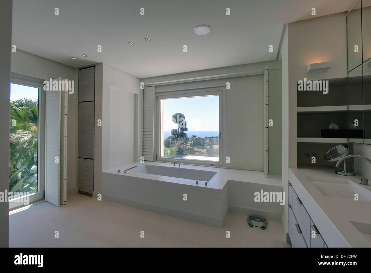 Fenster über Bad im weißen spanischen Badezimmer mit weißen ...