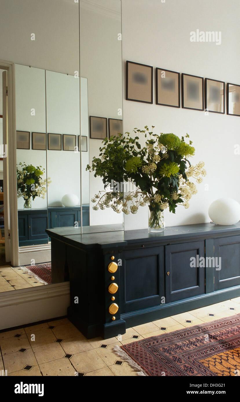 Verspiegelte Wand Hinter Niedrigen Blau Grau Schrank Mit Großen  Blumengesteck In Moderne Halle Mit Fliesenboden