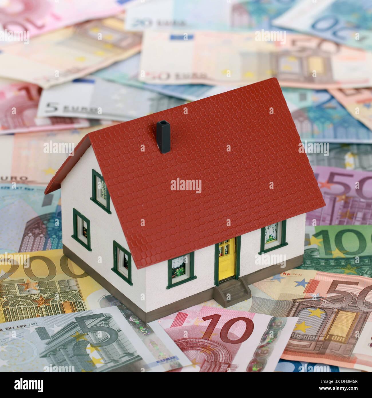 Symbolisches Bild eine Immobilienfinanzierung mit einem Haus auf Banknoten Stockbild