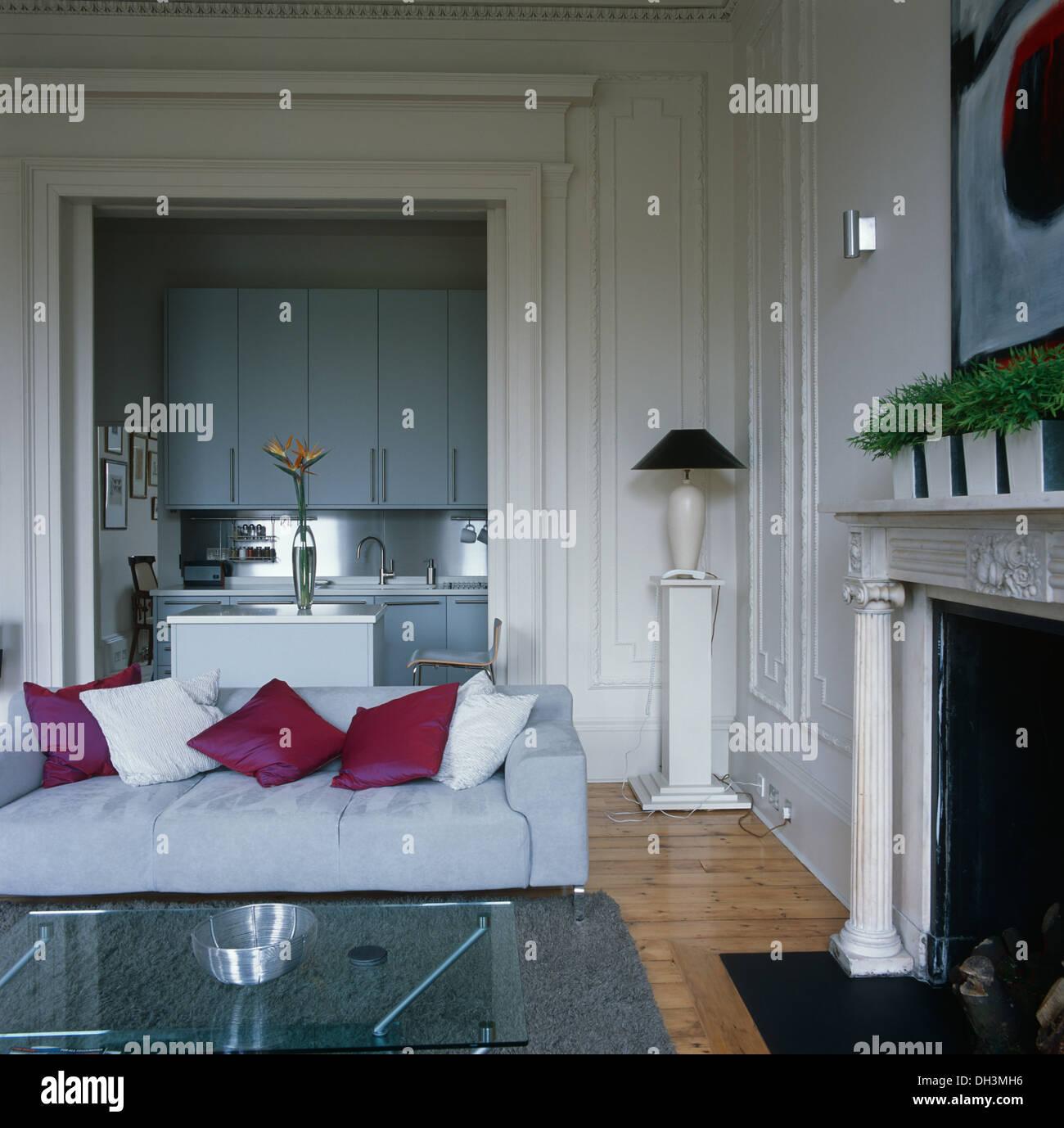 Rosa Seidenkissen auf weißen Sofa am Kamin in weiß getäfelten ...