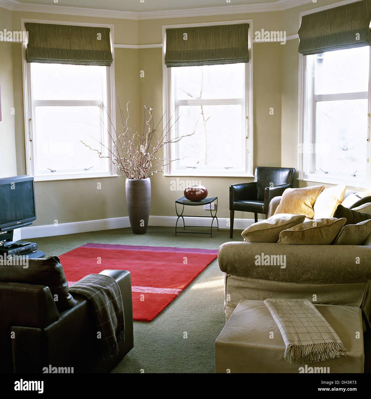 Beige Sofa Und Hocker Im Modernen Apartment Wohnzimmer Mit Römischen  Jalousien An Erker Und Roten Teppich Auf Grauen Teppich