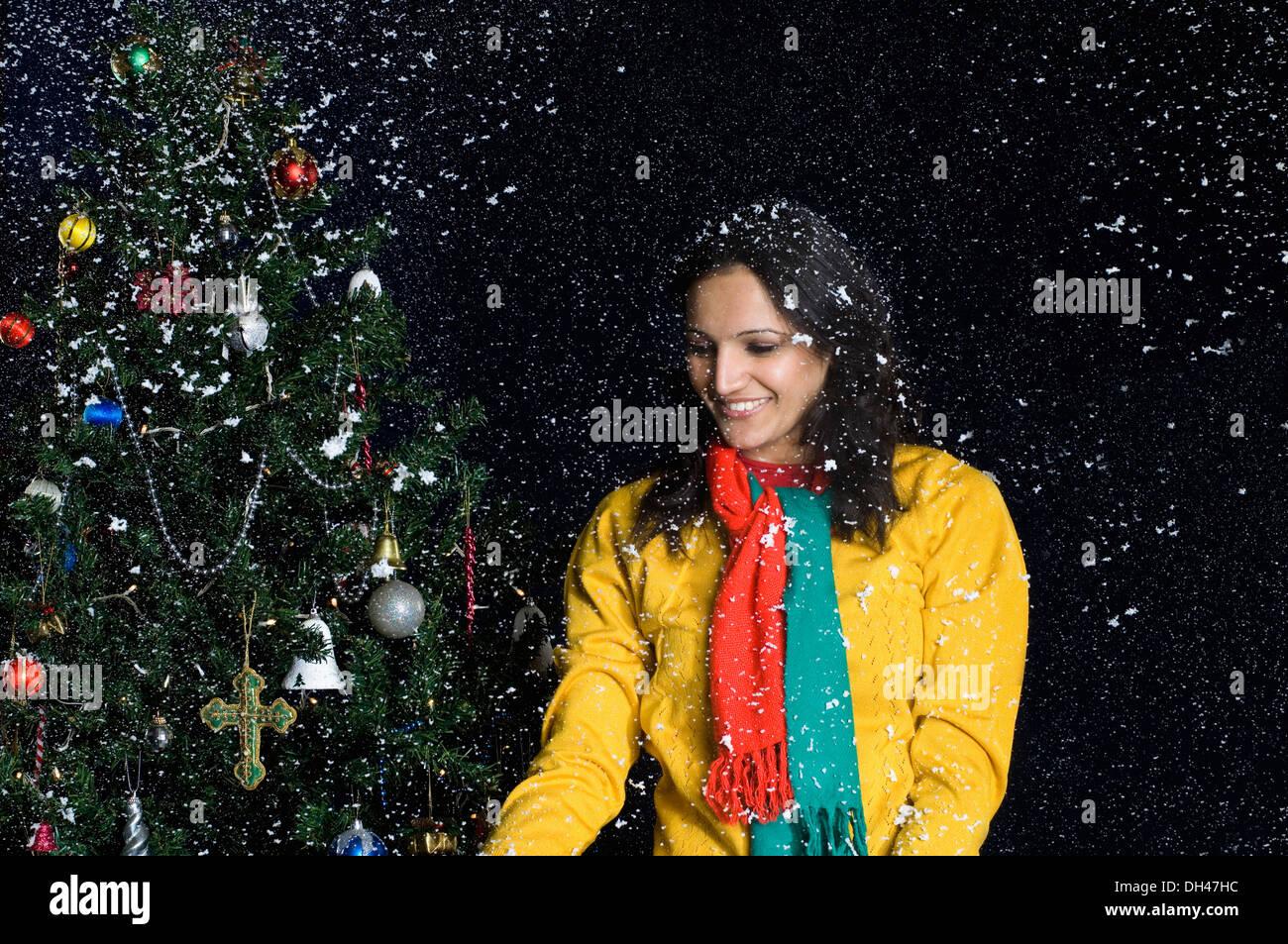 Frau im Schnee in der Nähe von einem Weihnachtsbaum Stockfoto