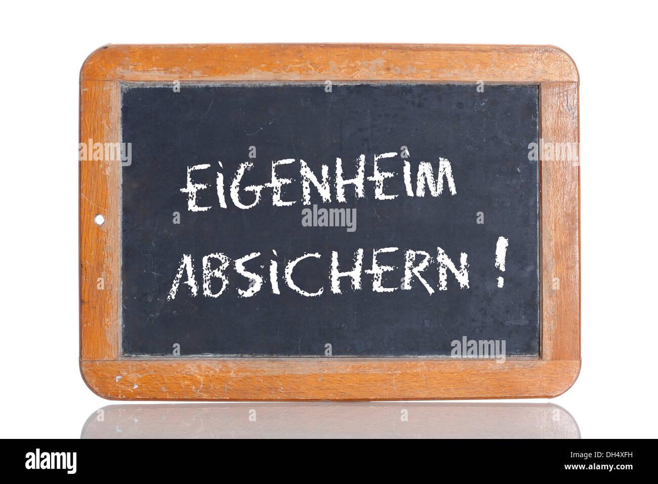 Alte Schultafel mit den Worten EIGENHEIM ABSICHERN!, Deutsch für bieten Sicherheit für Ihr Zuhause! Stockbild