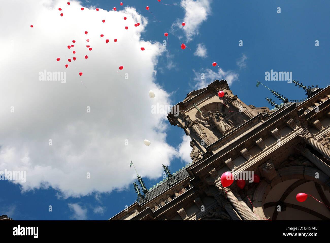 rote Luftballons über das historische Rathaus Stockbild