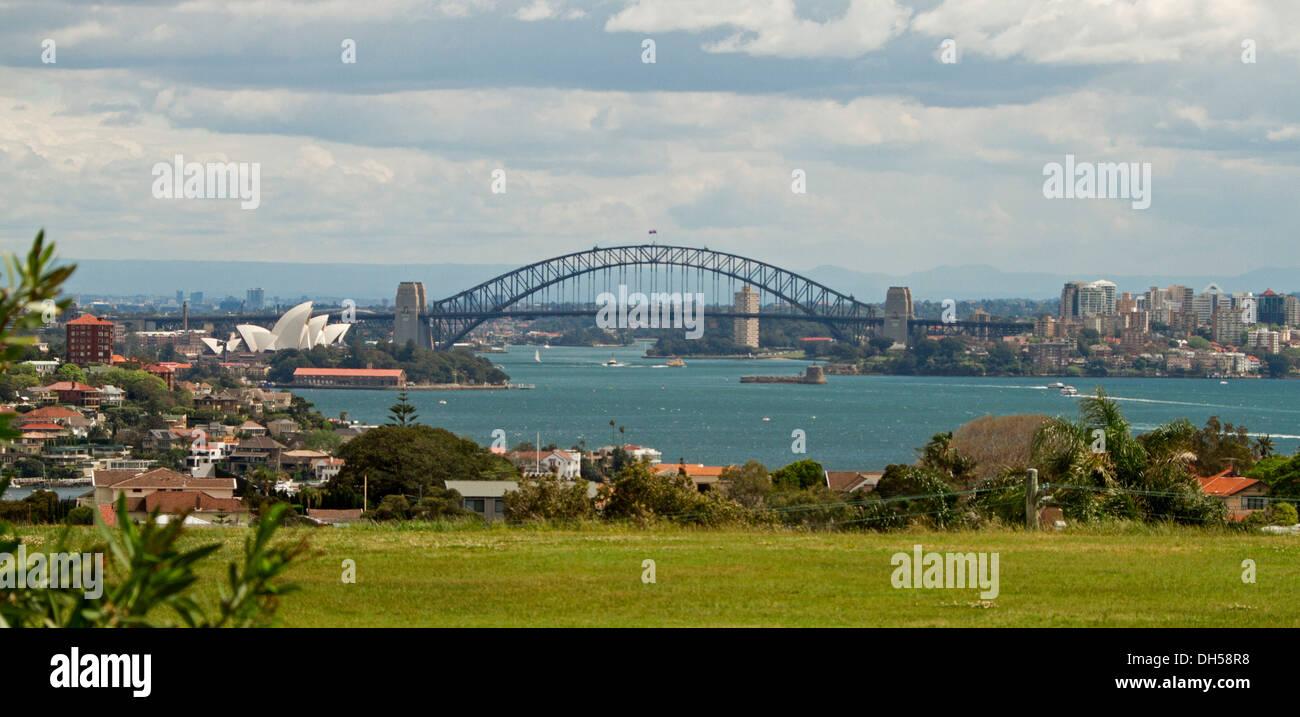 Panoramablick auf die Stadt-Landschaft zeigt Sydney Harbour Bridge, berühmte Oper und Häuser am blauen Wasser des Stockfoto