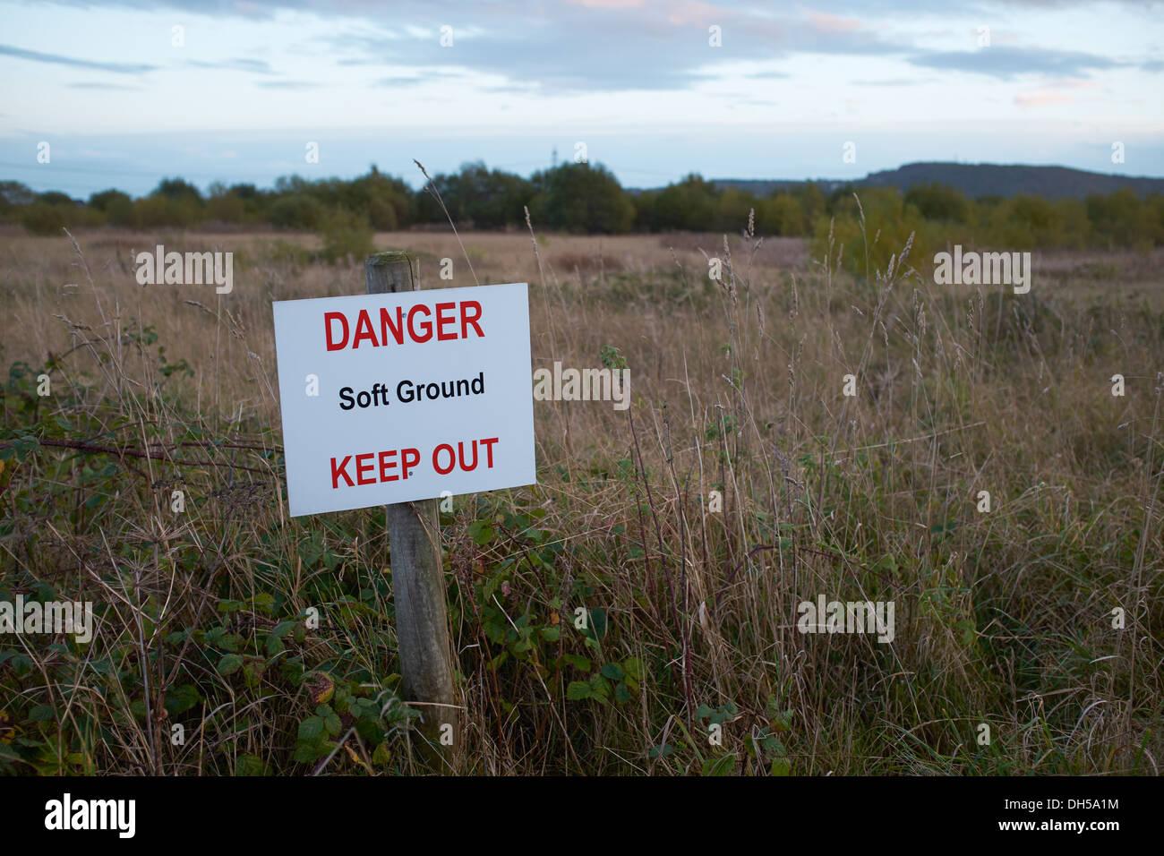 Gefahrenzeichen, weichen Boden zu halten, neben eine bewachsene Fläche Stockbild