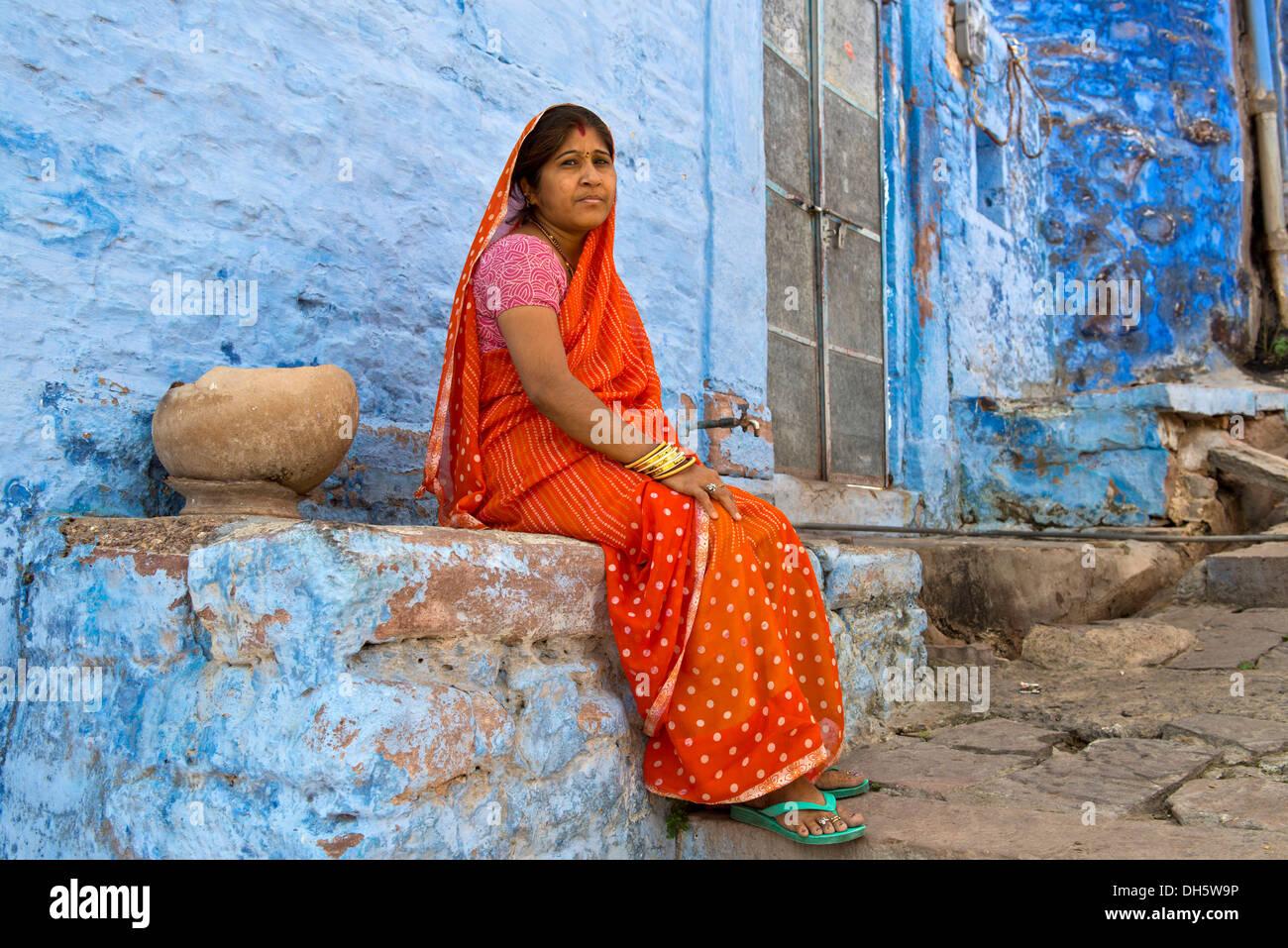 Ältere Frau trägt einen roten Sari sitzt auf einem Felsvorsprung ein blau lackiert, Wohngebäude, Brahmpuri, Jodhpur, Rajasthan, Indien Stockfoto