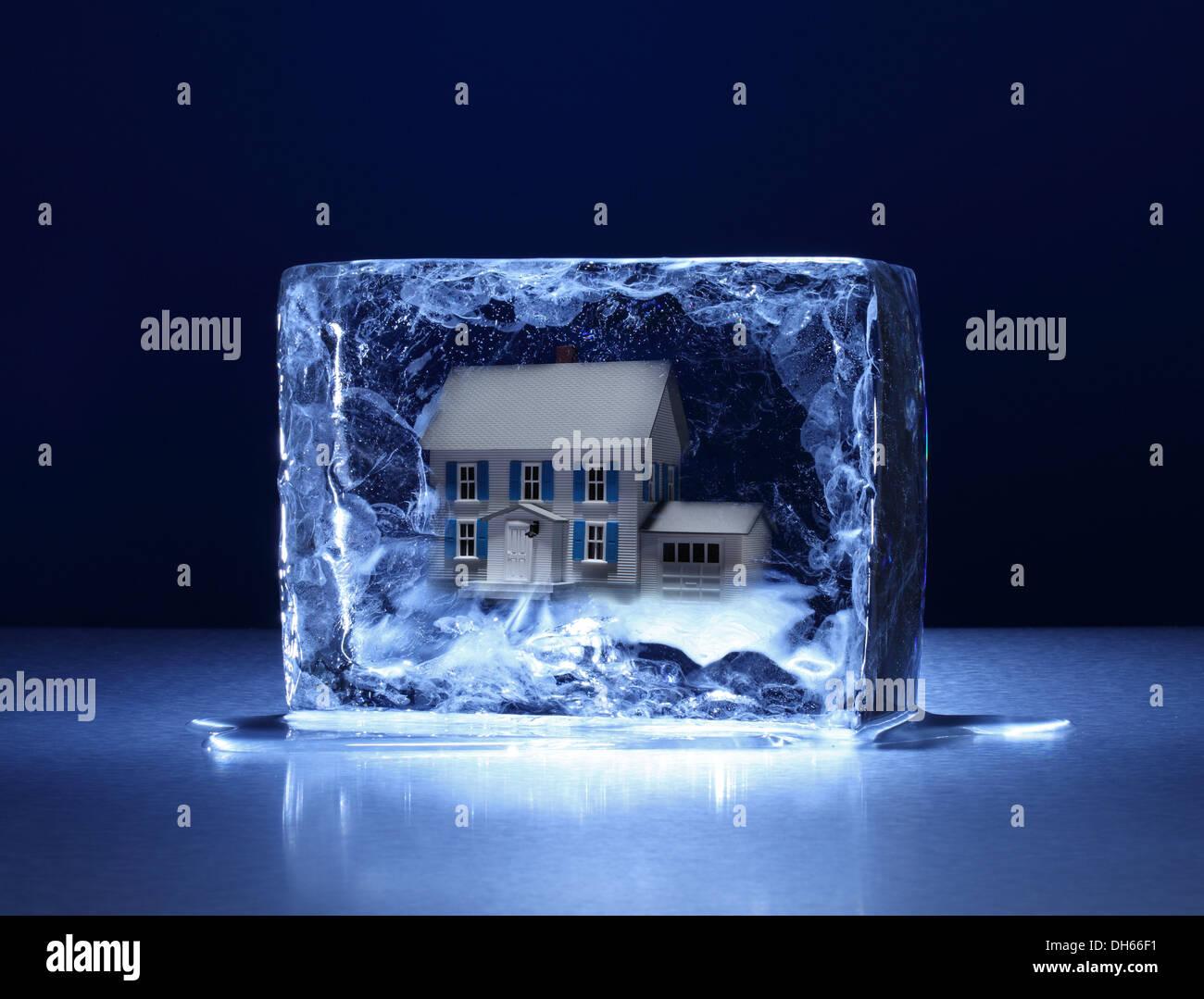 Ein Musterhaus in einem klaren Eisblock eingefroren Stockbild