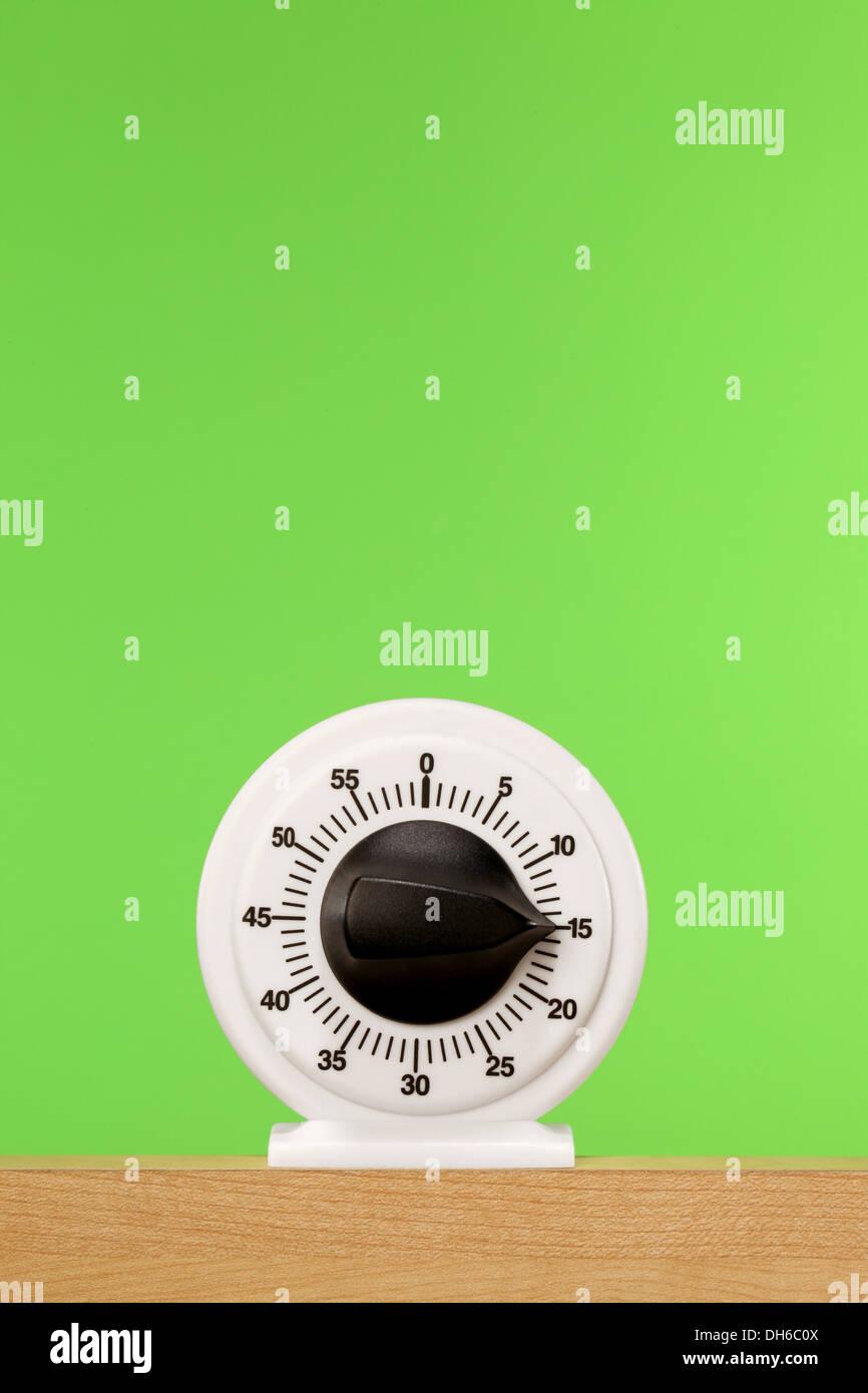 Eine Stoppuhr auf einem Holzregal mit leuchtend grünem Hintergrund Stockbild