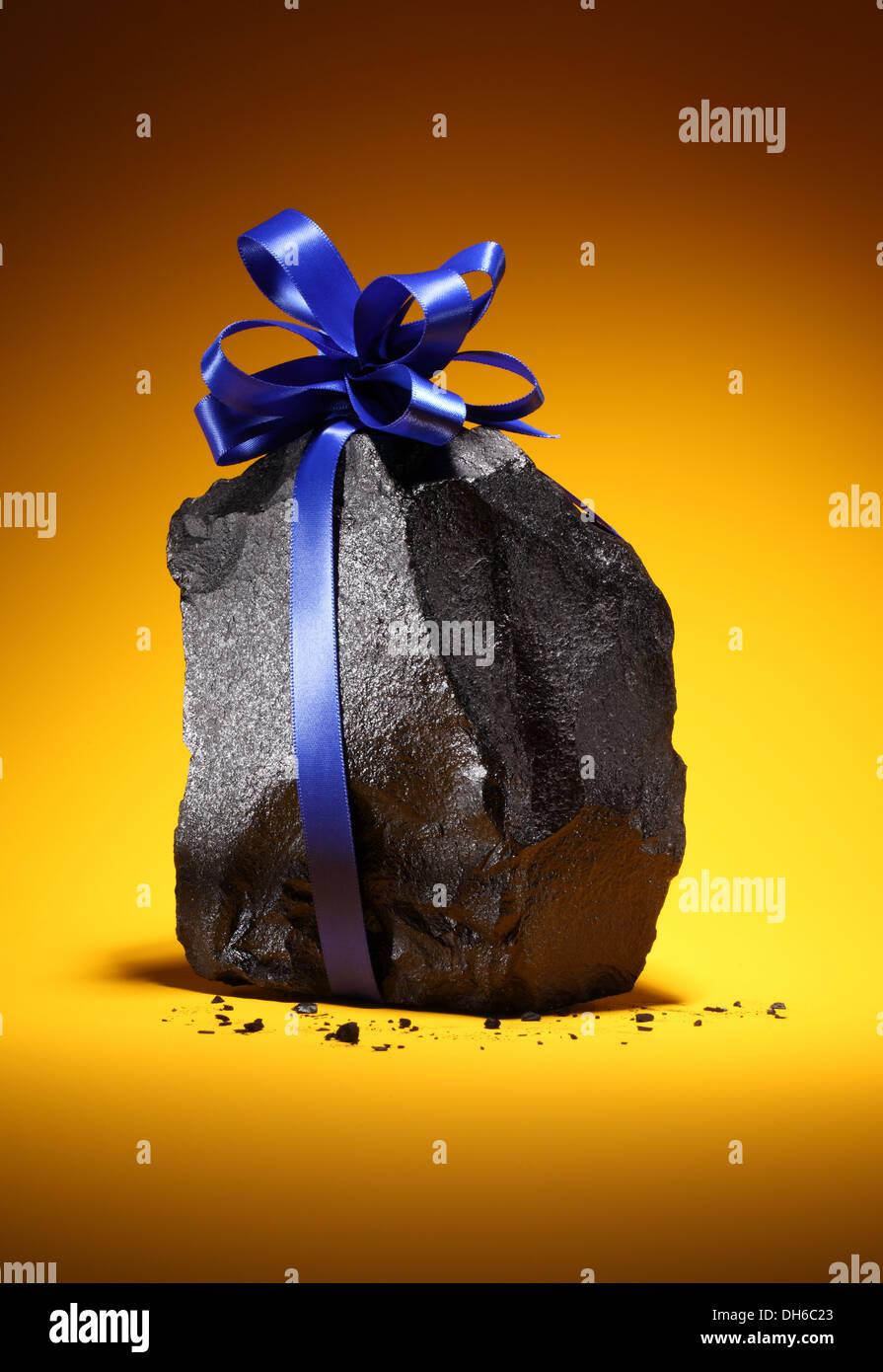Ein schwarzen schwarzen Klumpen Kohle mit einem blauen Band gebunden um ihn herum. Leuchtend orange Hintergrund. Stockbild