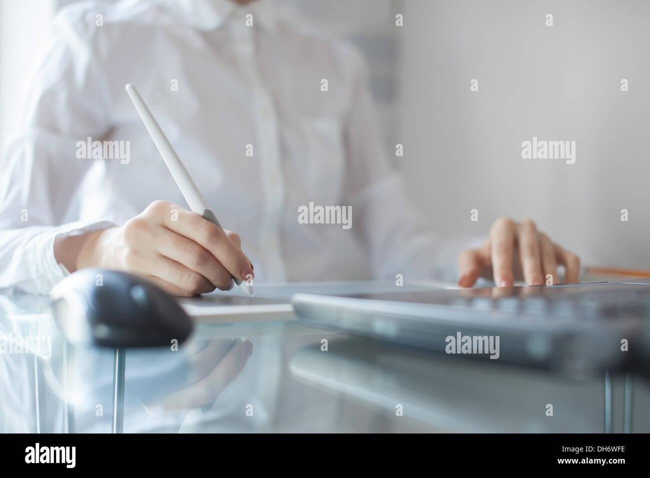 Designerin mit Grafiken Pad im Büro Stockbild