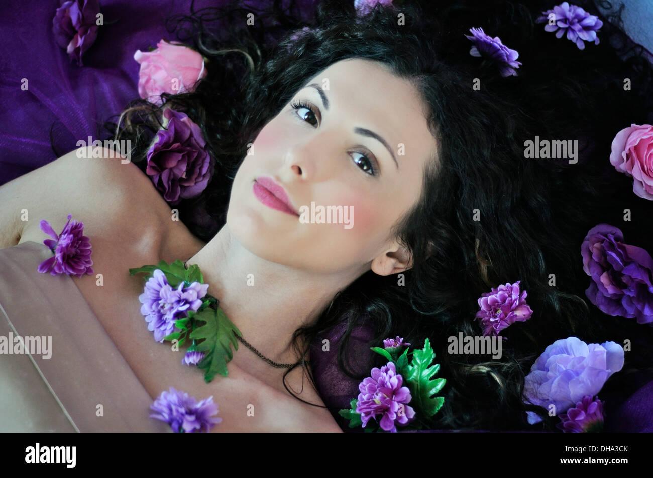 Porträt einer jungen schönen Frau auf Bett liegend Stockbild