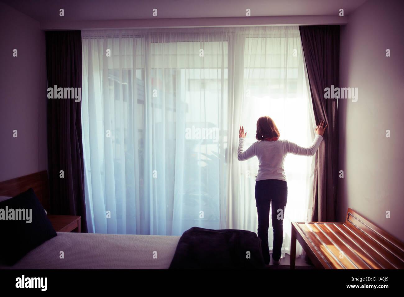 Frau schaut aus Schlafzimmer Glastüren Stockfoto
