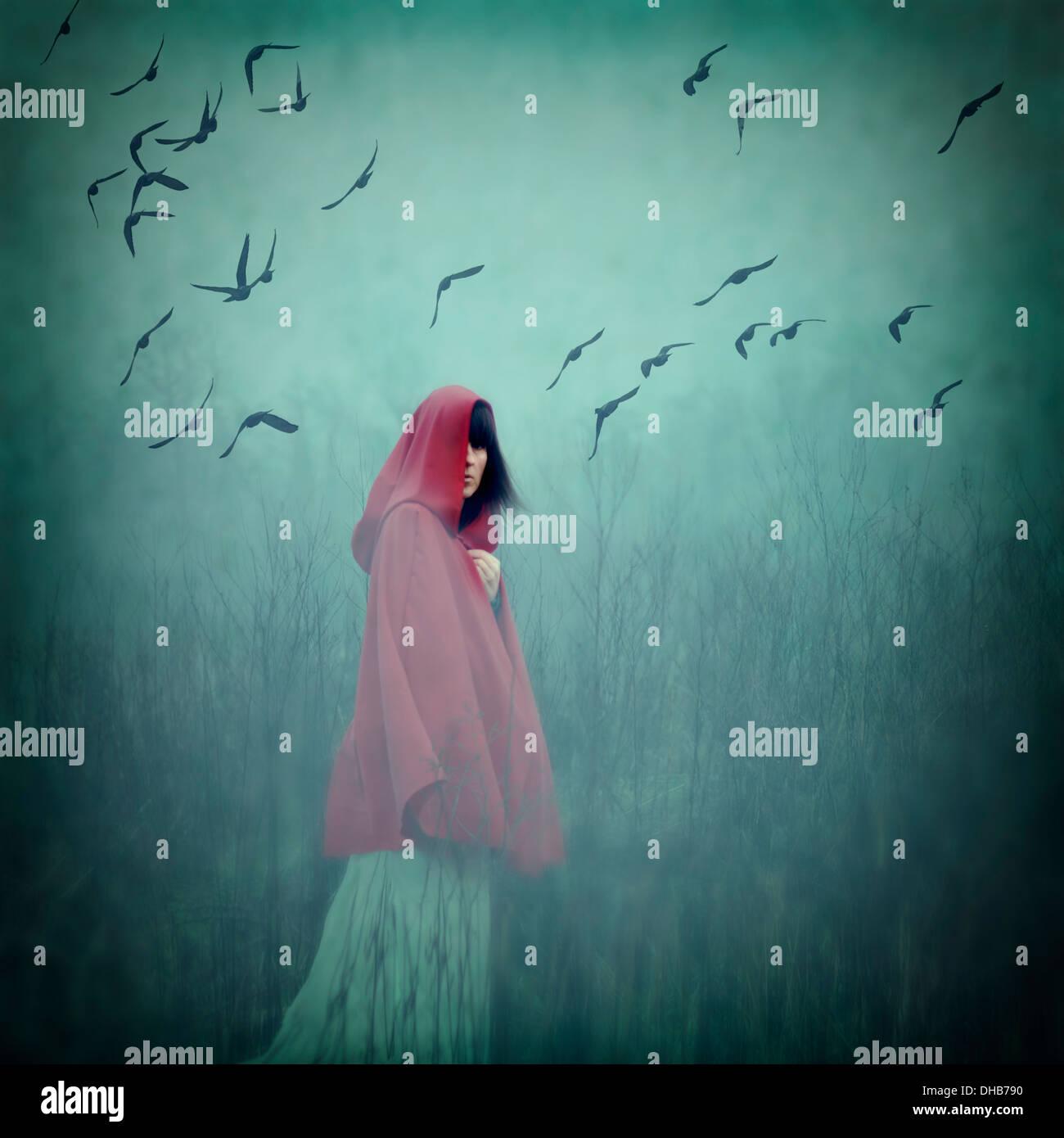 Frau mit roten Umhang walking im freien Stockbild