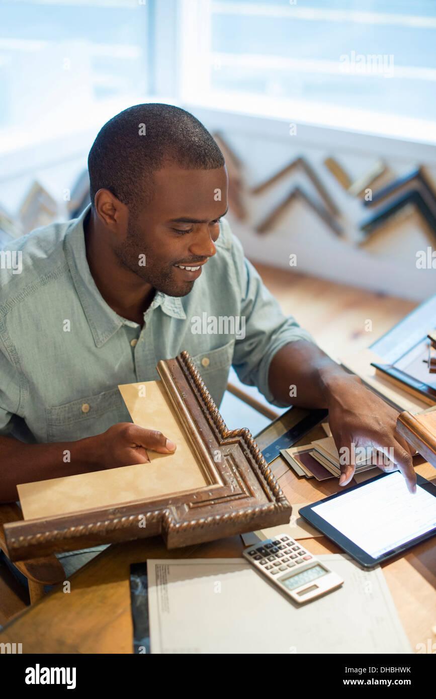 Ein junger Mann an seiner Werkbank in einem Bild Framing Studio ...