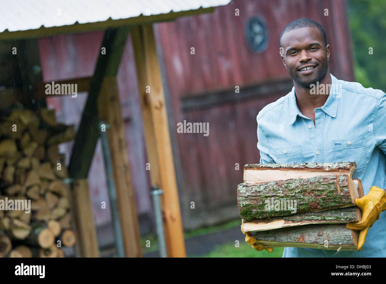 Ein junger Mann mit einem Haufen der Protokolle in der Logstore. Leben auf dem Bauernhof. Stockbild