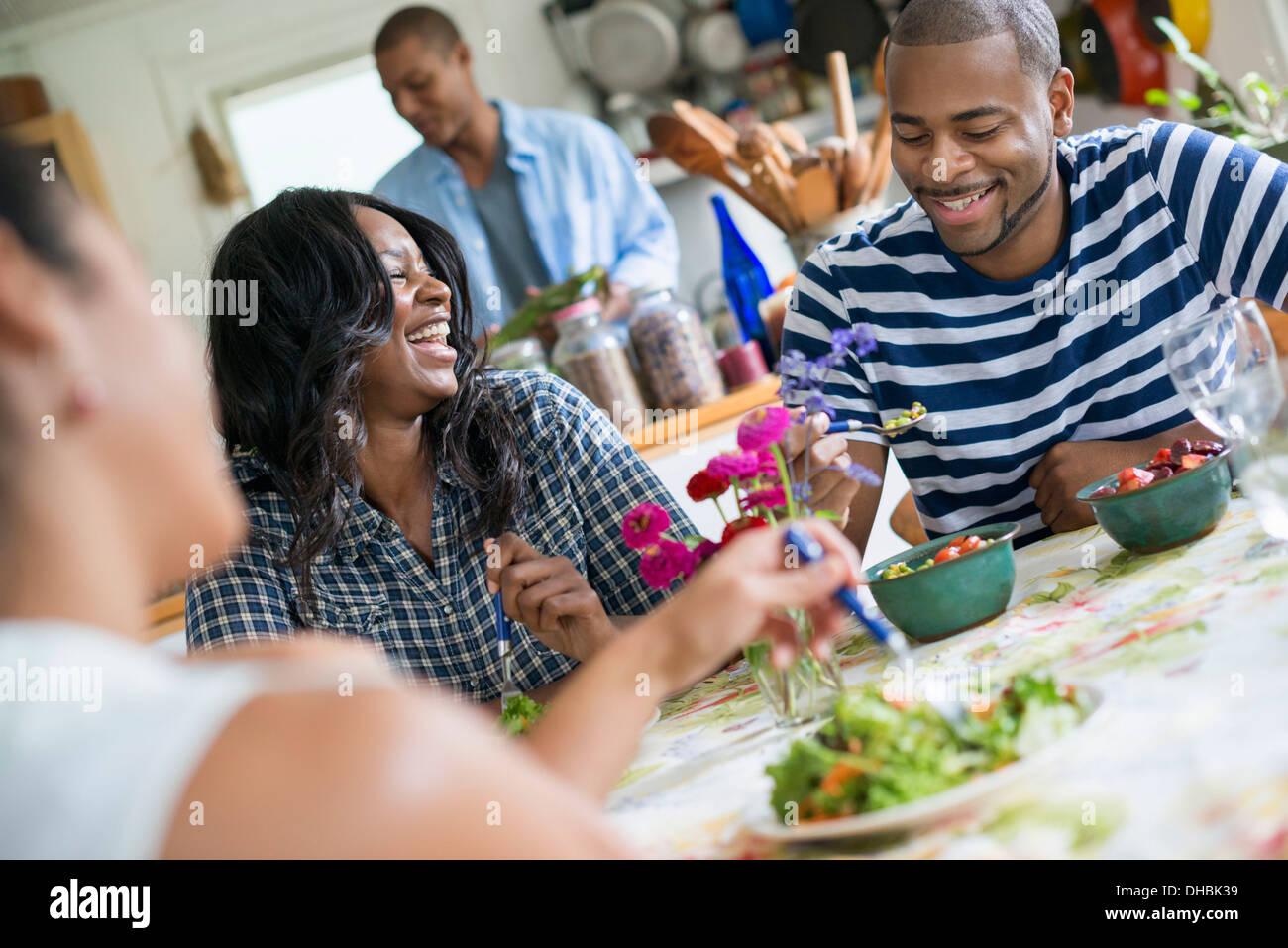 Eine Gruppe von Frauen und Männern bei einer Mahlzeit in einer Landhausküche. Stockbild