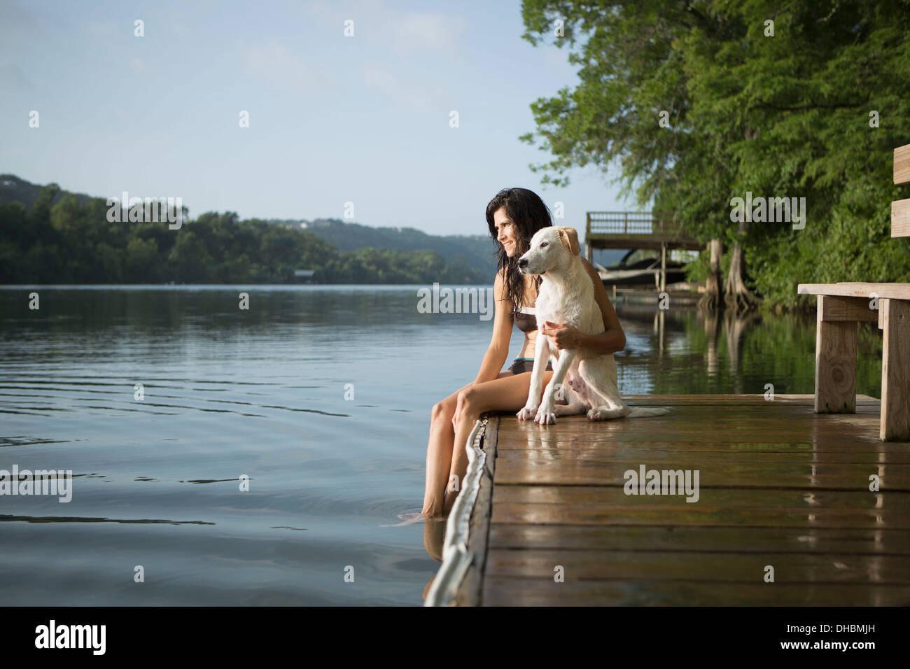Eine Frau mit ihren Arm um einen kleinen weißen Hund auf einem Steg am See. Stockbild