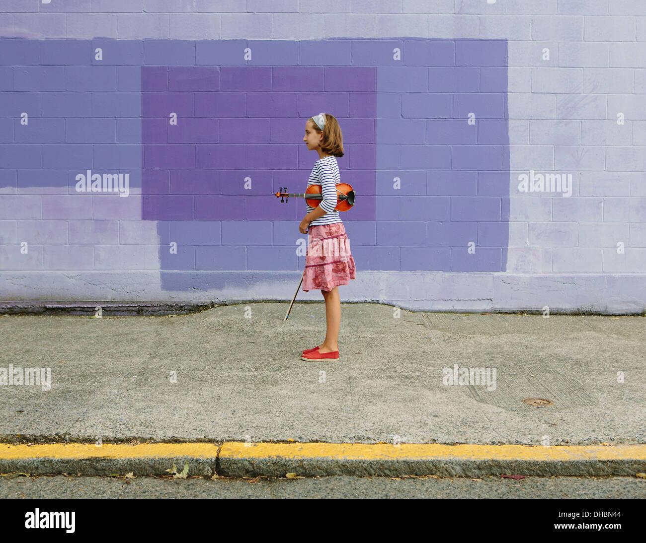 Ein zehn Jahre altes Mädchen mit einer Geige unter dem Arm und einen Bogen in der Hand. Lila Hintergrund. Stockbild