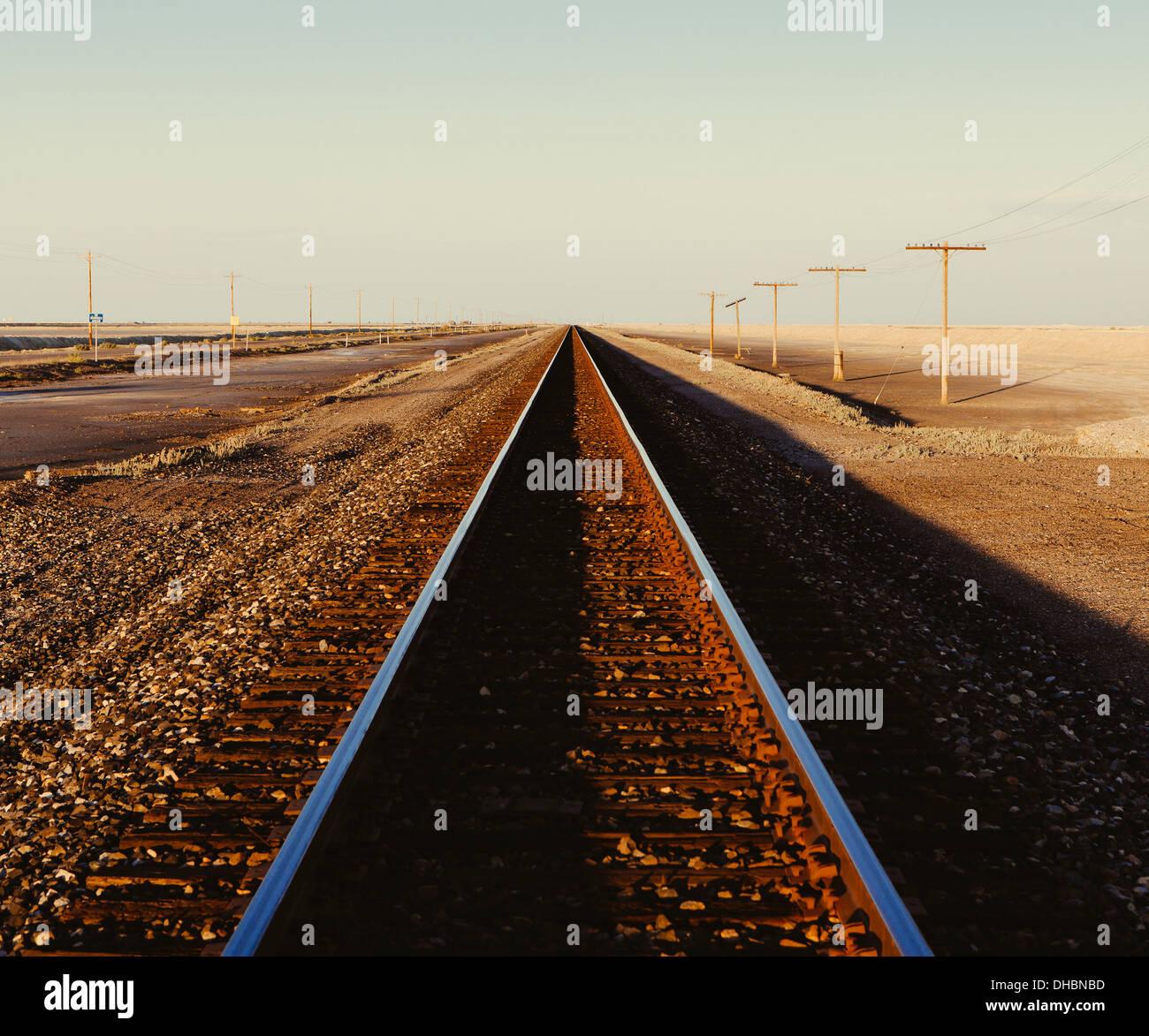Eisenbahnschienen erstreckt sich über die flache Wüstenlandschaft von Utah in der Abenddämmerung. Stockbild