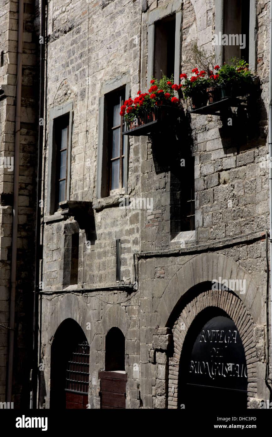 Wand einer Straße mit Blumenkästen in Gubbio, Italien Stockfoto ...