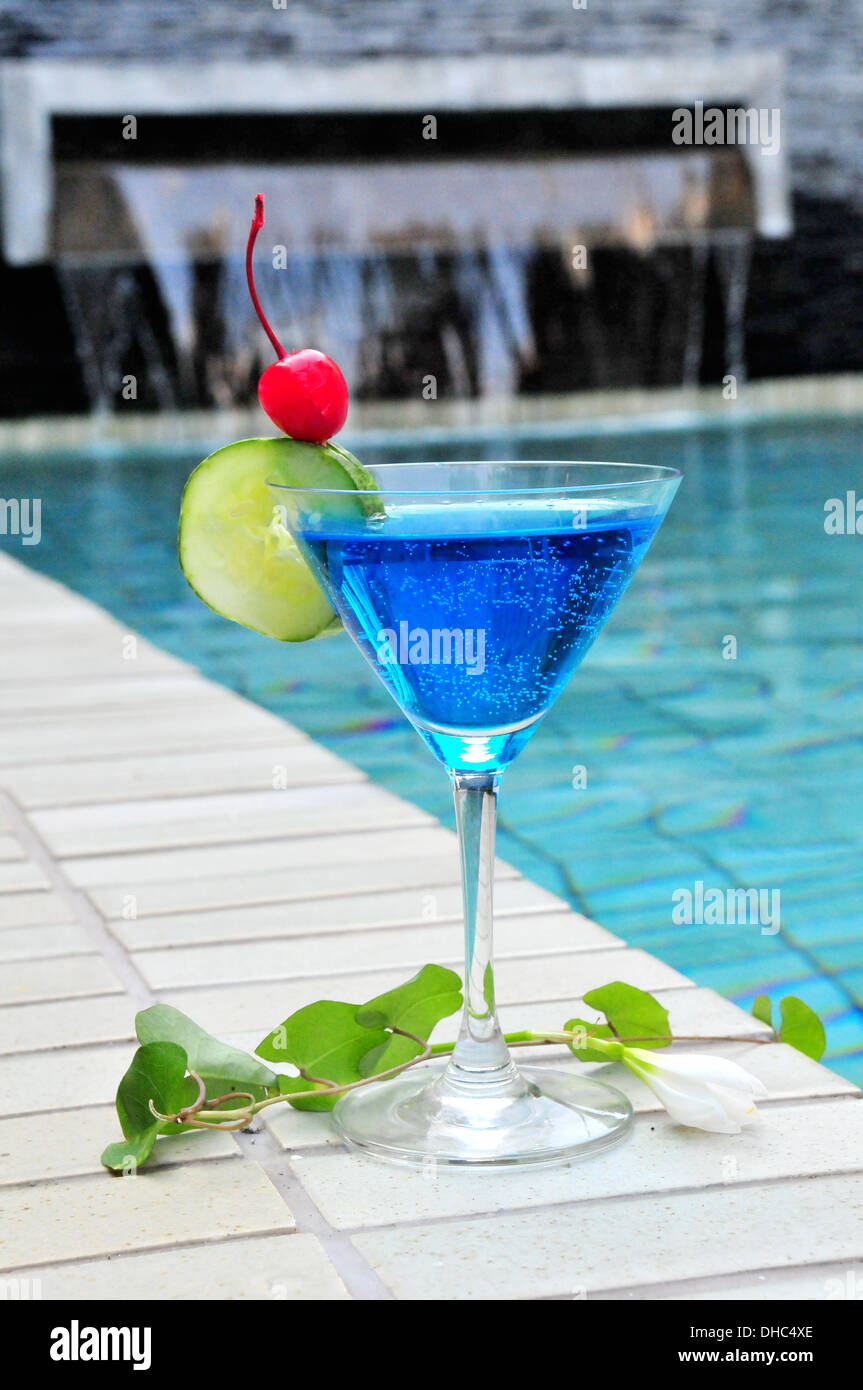 Ein Glas blue cocktail Drink am pool Stockbild