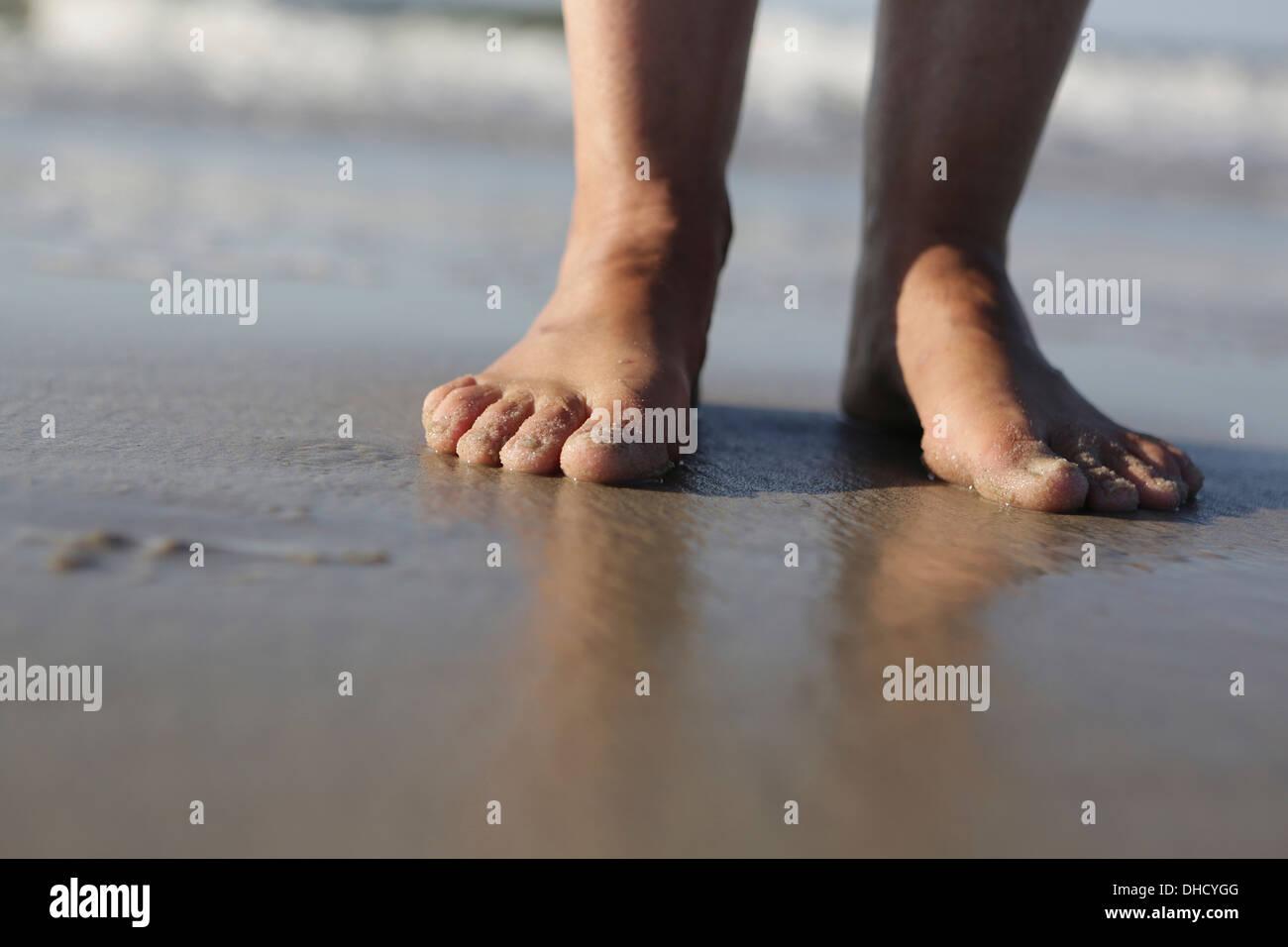 Deutschland, Niedersachsen, Ostfriesland, Langeoog, Füße einer Frau am Strand Stockbild