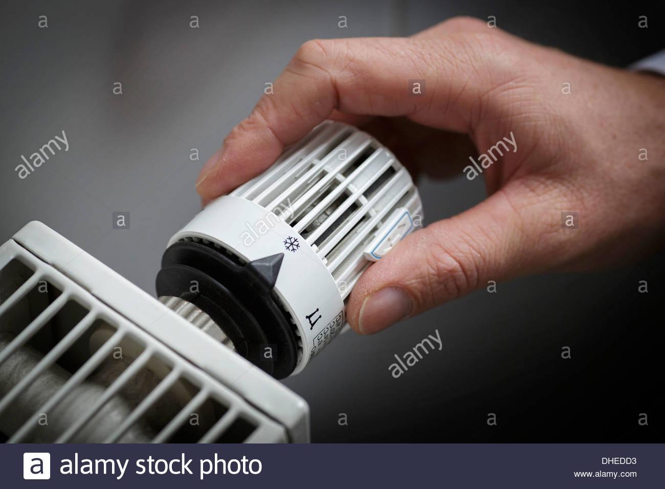 Menschliche Hand, die Steuerung eines Heizkörpers Stockbild