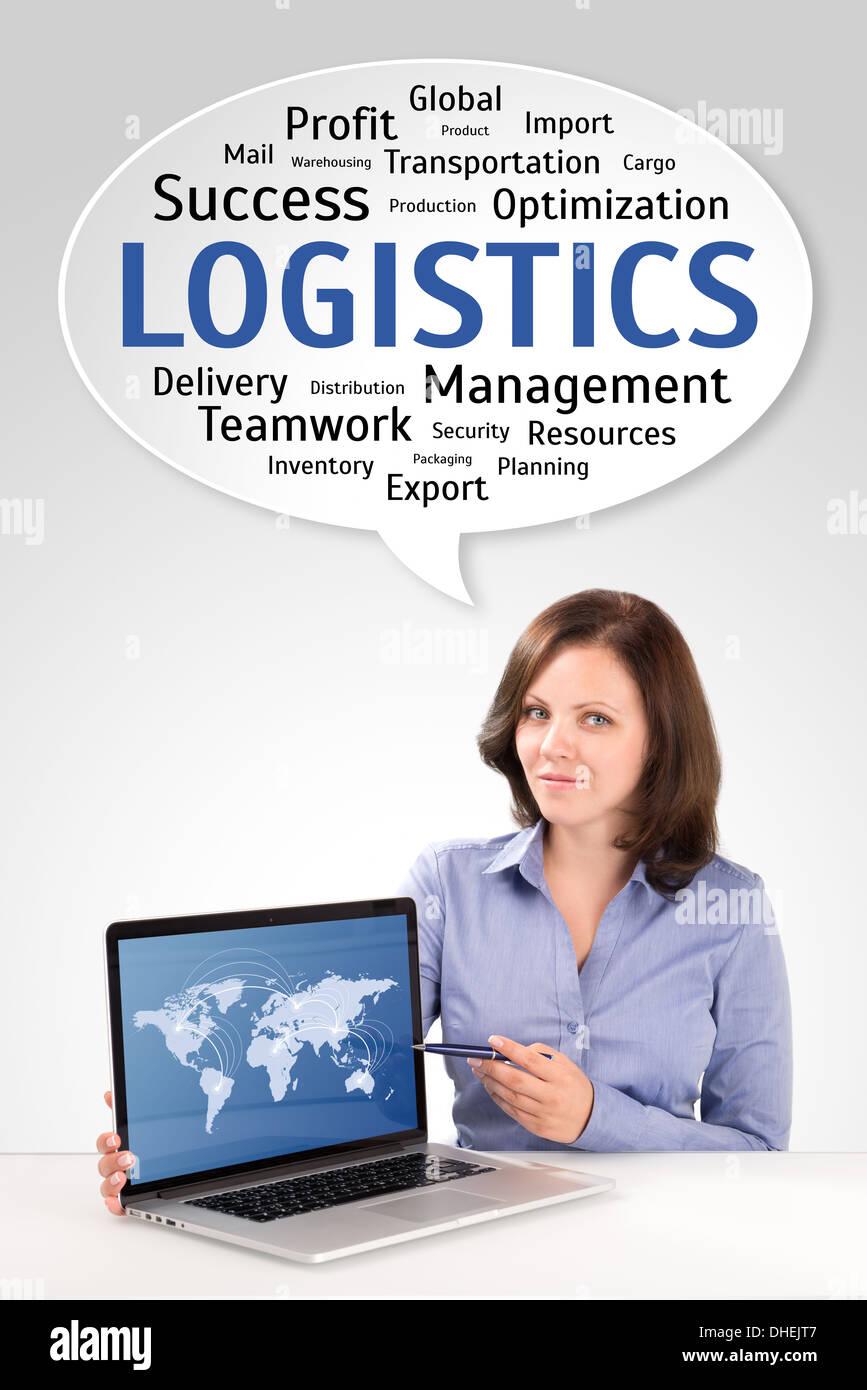 Logistik-Manager zeigt Weltkarte auf einem Laptop-Bildschirm unter Technologie Wordcloud, Business-Konzept Stockfoto