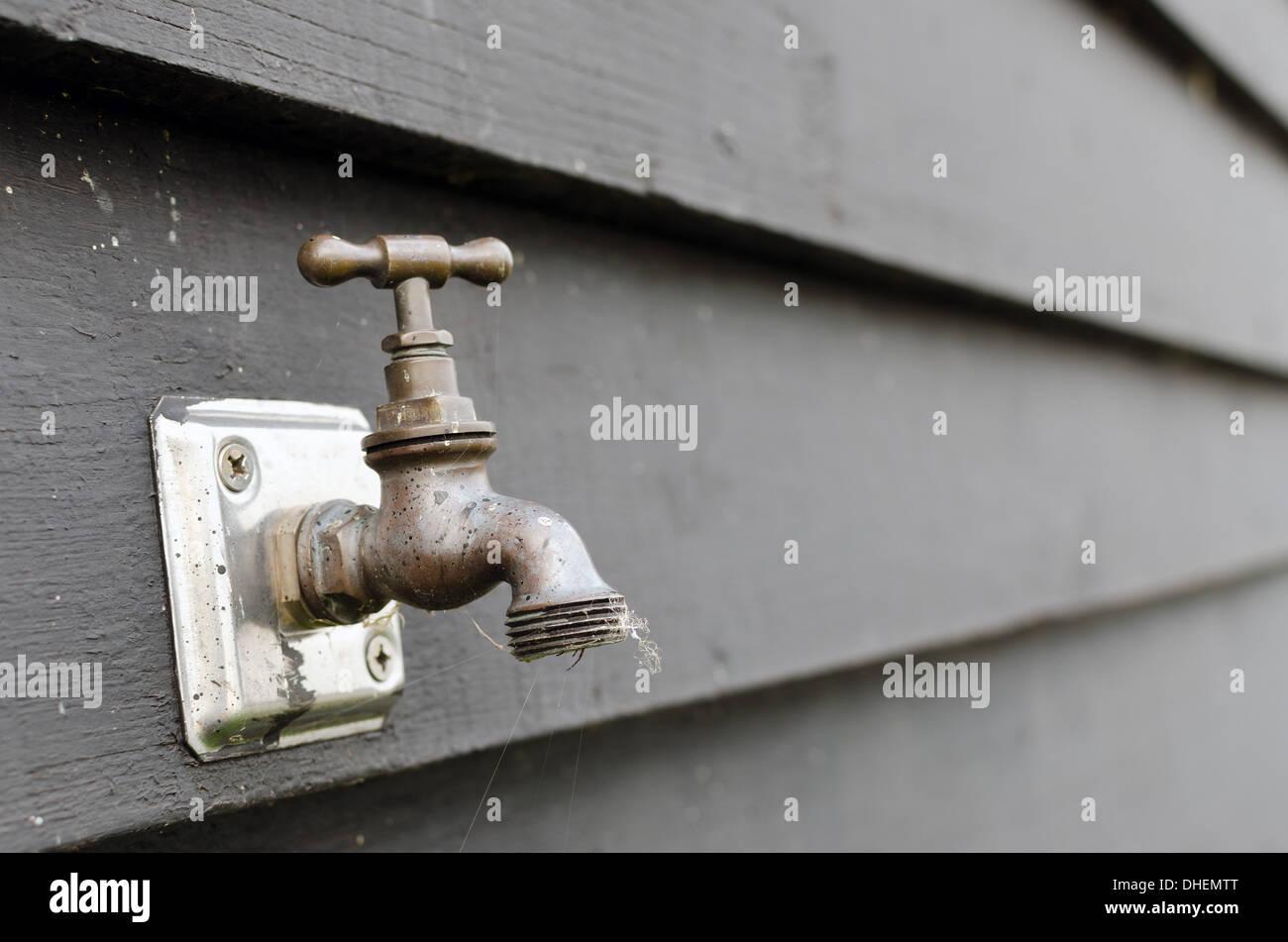 Wetter Geschlagen Outdoor Wasserhahn Gegen Eine Schwarze Holzwand