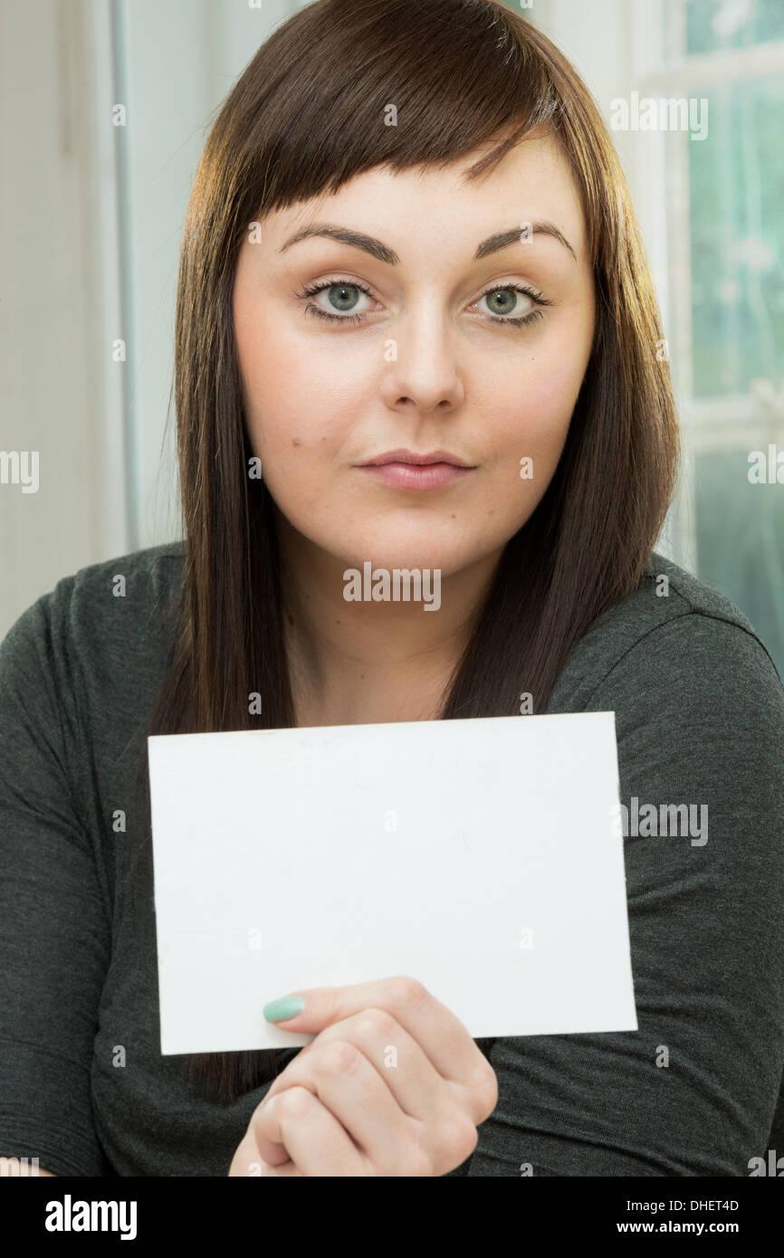 Ernste junge Frau mit einer leeren Karte Stockbild