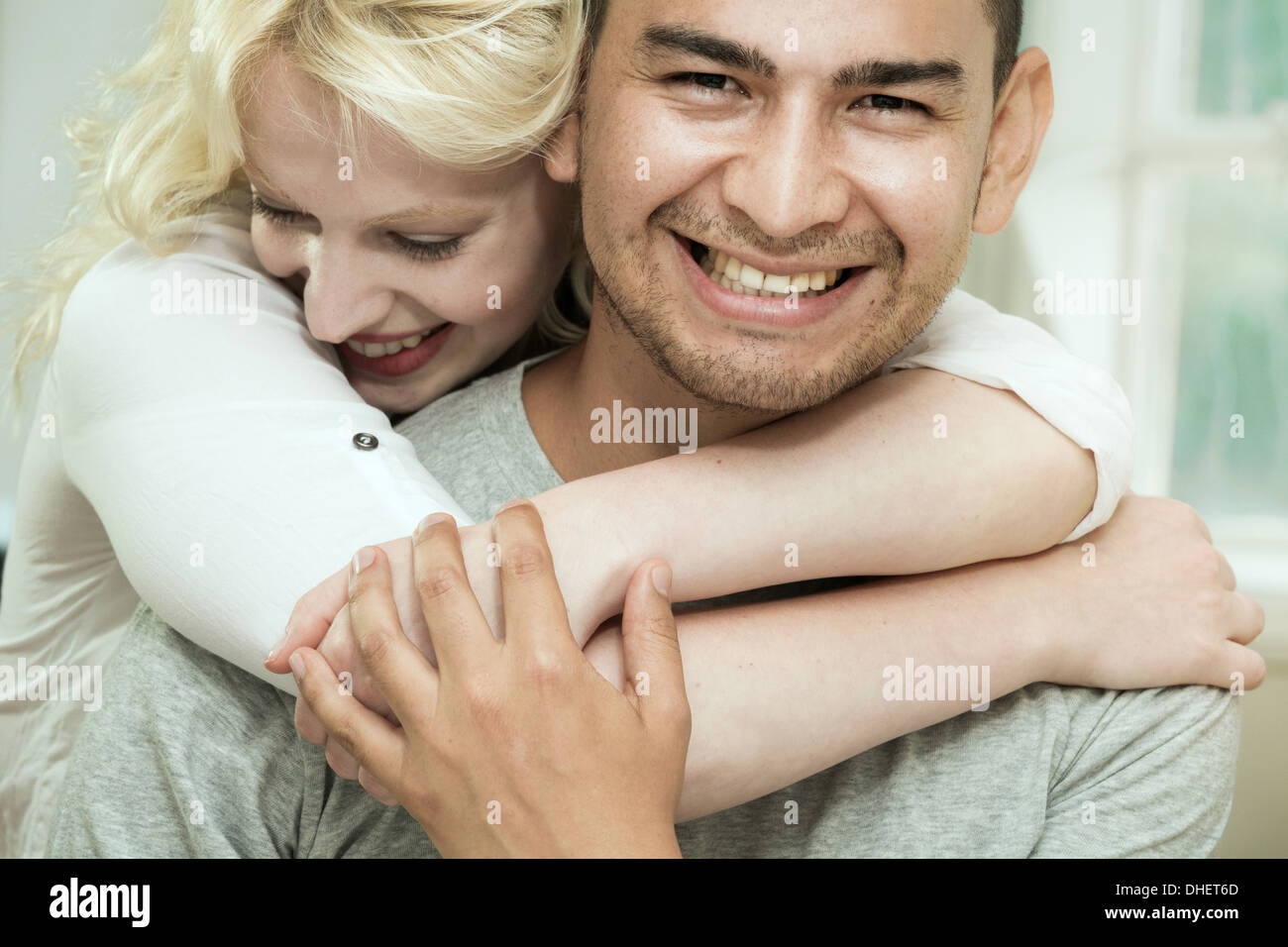 Junge Frau umarmt Freund Stockfoto