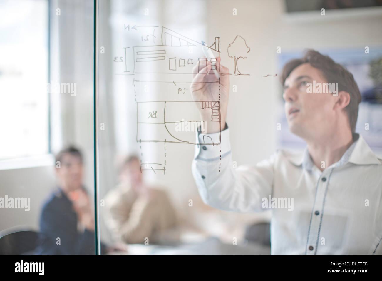 Menschen zeichnen Baupläne an Glaswand, Kolleginnen und Kollegen im Hintergrund Stockbild