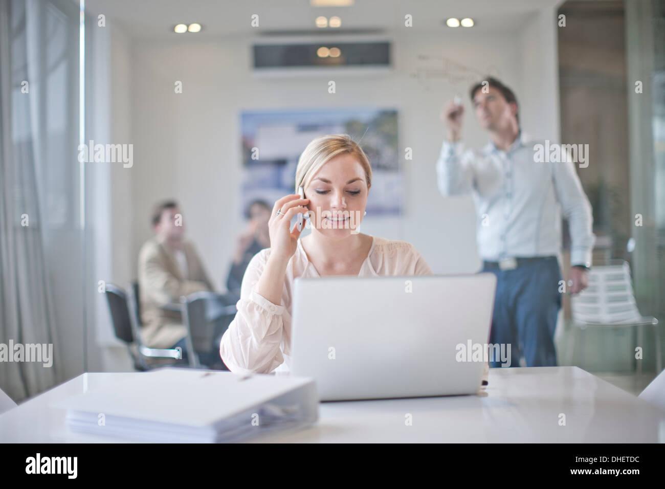 Frau sitzt am Konferenztisch mit Laptop und Handy, im Hintergrund arbeitenden Kolleginnen und Kollegen Stockbild