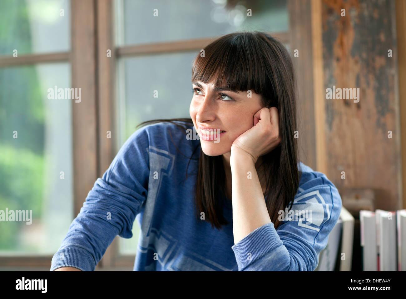 Porträt von Brünette Frau lächelnd mit Hand am Kinn Stockbild