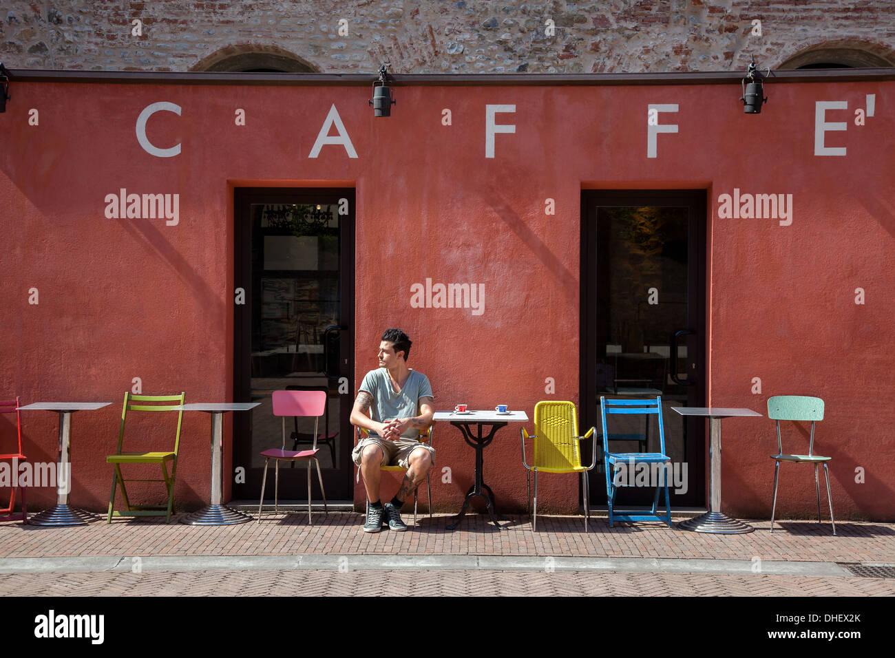Junger Mann sitzt vor Café, Florenz, Toskana, Italien Stockbild