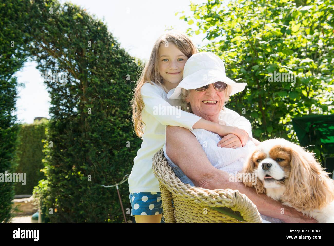 Porträt der Großmutter und Enkelin mit Hund Stockbild