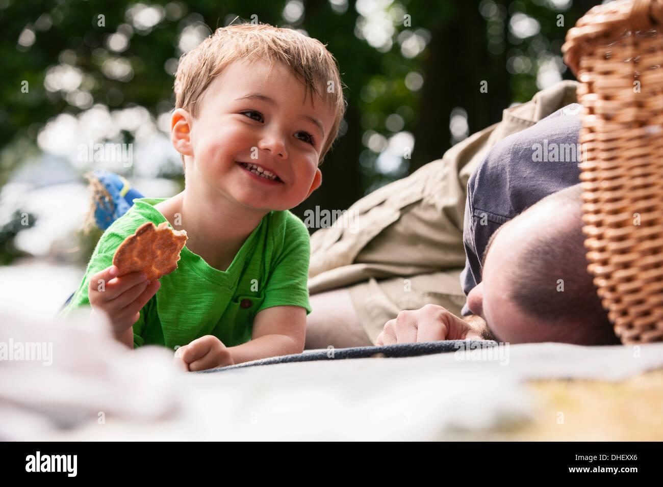 Junge genießt Picknick mit Vater Stockbild