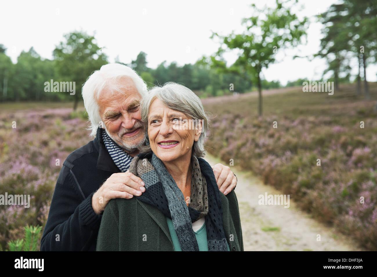 Älteres Paar, Mann mit Händen auf Frau Schultern Stockfoto