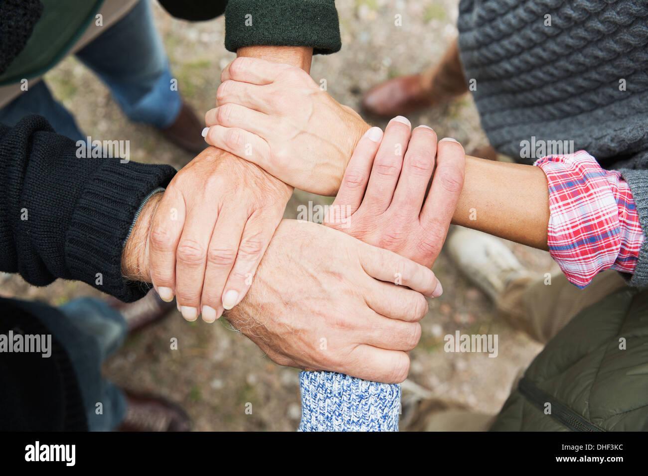 Vier Menschen berühren, Hände, hohe Winkel Stockbild