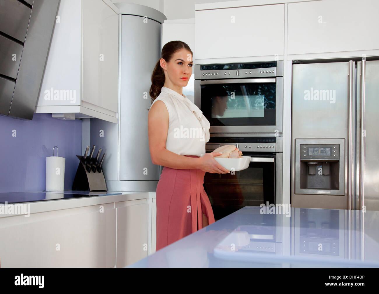 Junge Frau mit Bräter in Küche Stockbild