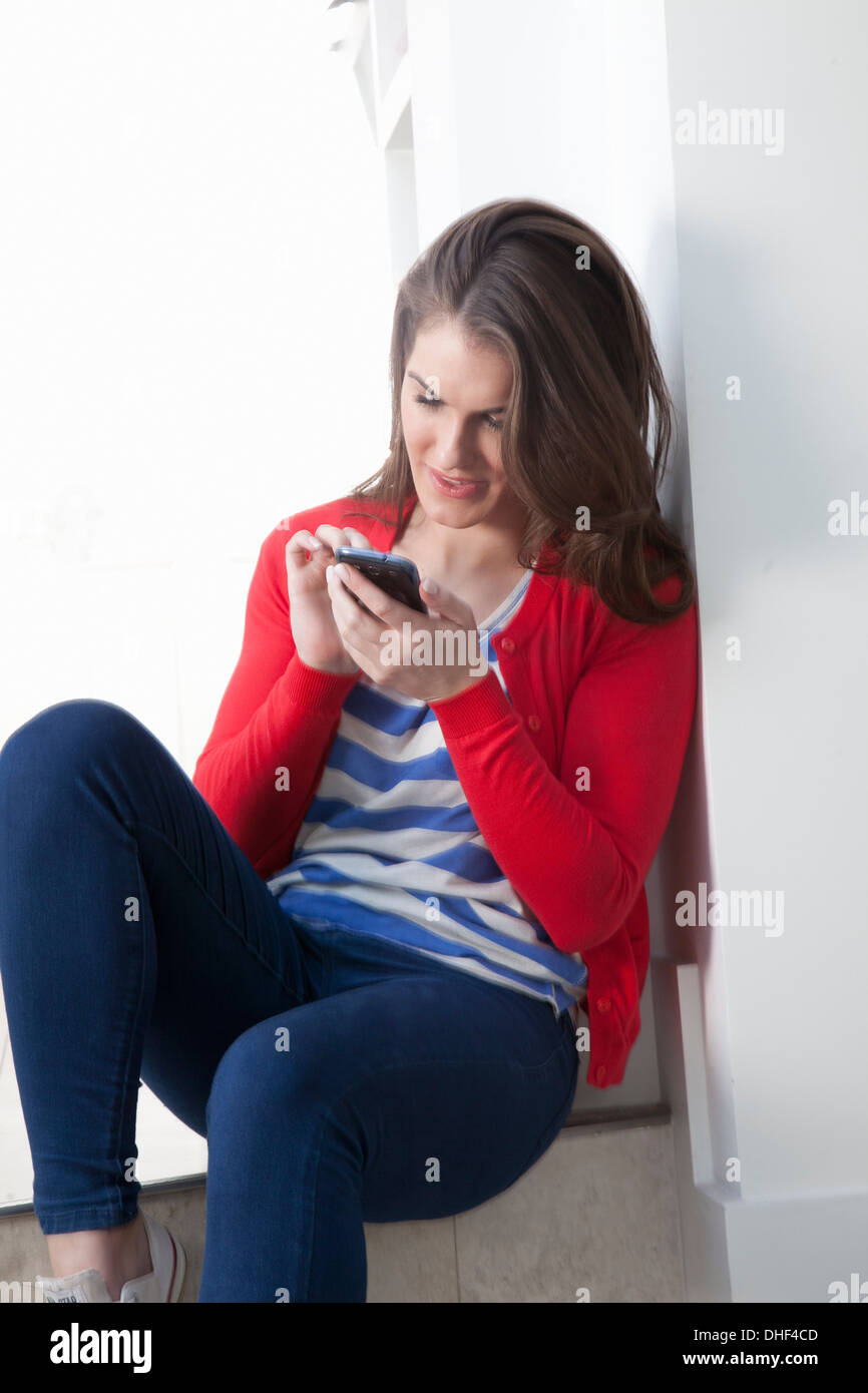 Junge Frau sitzt auf Schritt mit Handy Stockbild
