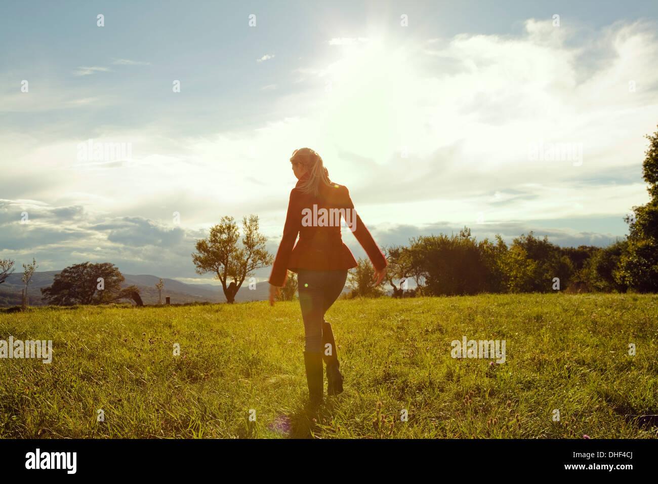 Junge Frau im Feld zu Fuß entfernt Stockbild