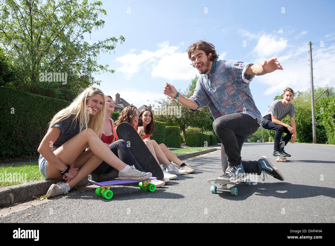 Vier junge Frauen sitzen auf Bordstein Skateboarder beobachten Stockbild