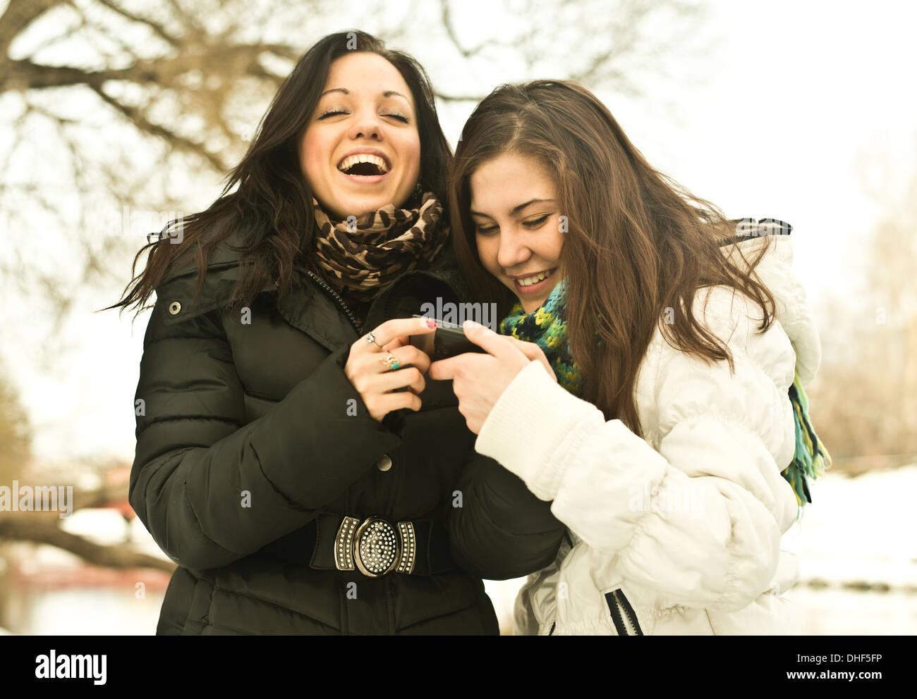 Zwei junge Frauen lachen über Handy im Park im winter Stockbild