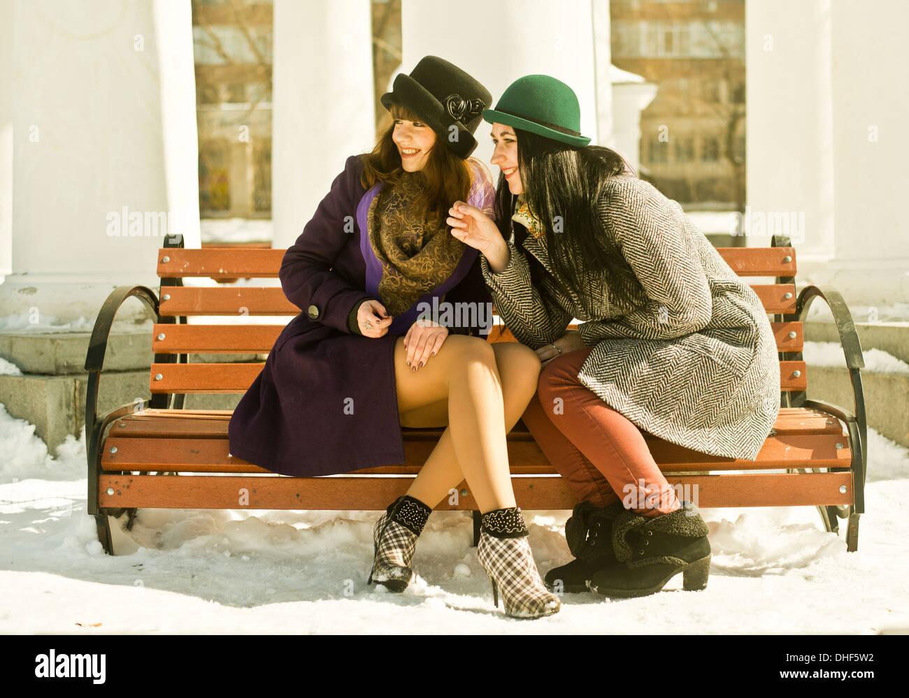 Zwei junge Frauen sitzen auf der Parkbank im Schnee Stockfoto