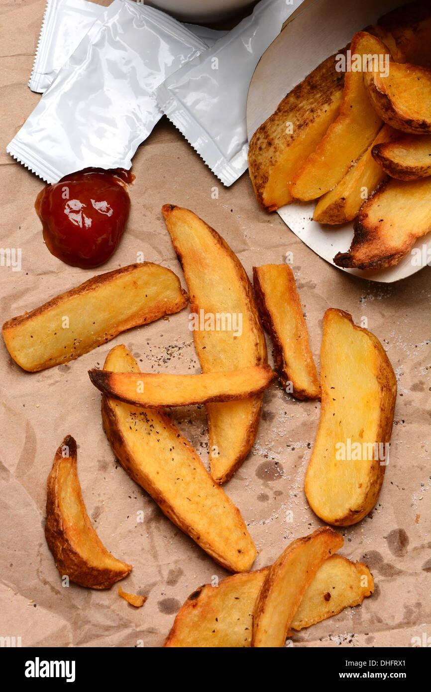 Pommes frites verschüttet auf eine braune Tasche. Klecks Ketchup und ...