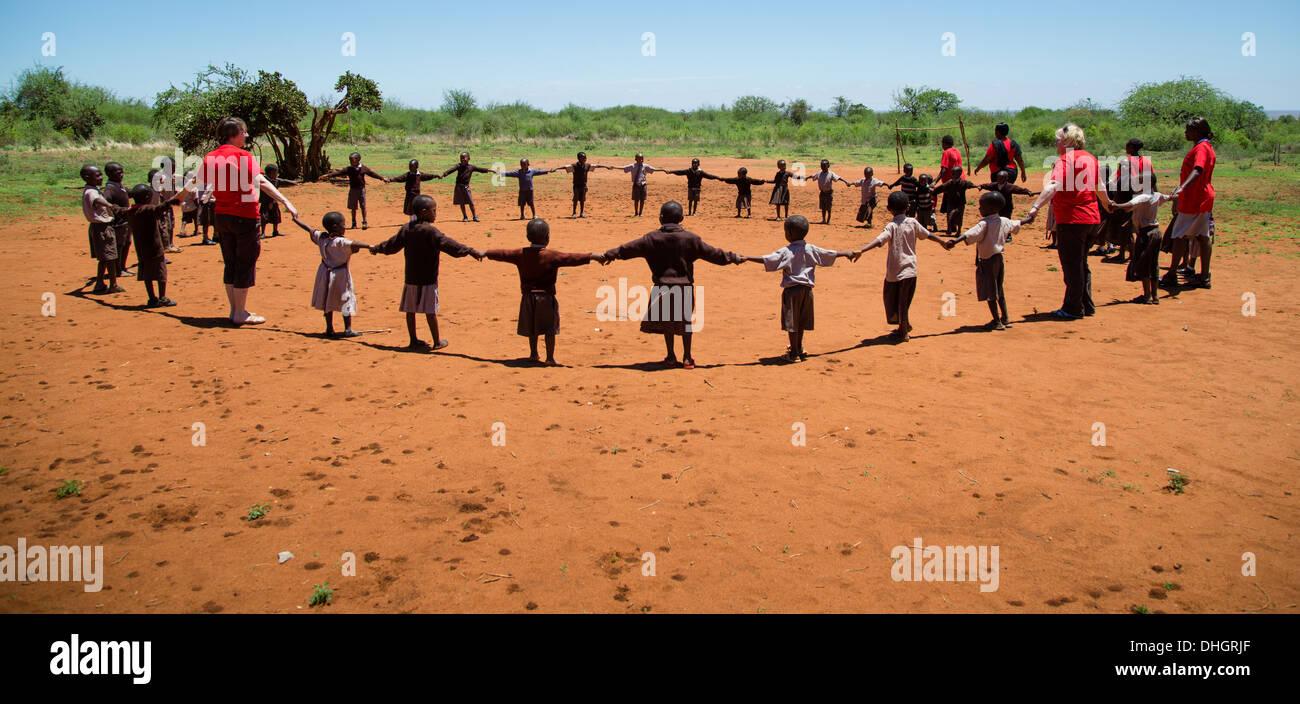 Schülerinnen und Schüler und Lehrer spielen hokey Cokey im kenianischen Spielplatz Stockbild
