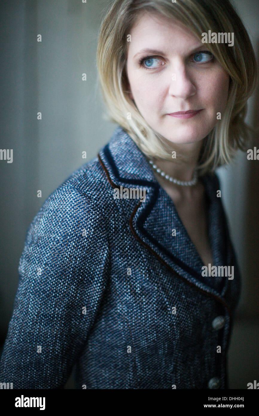Markante kaukasischen Frau in Perlen und Chanel Tweed Anzug auf mysteriöse Weise Blicke Stockbild